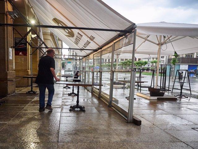 Un trabajador prepara la terraza del bar para la apertura en la Plaza del Castillo de Pamplona