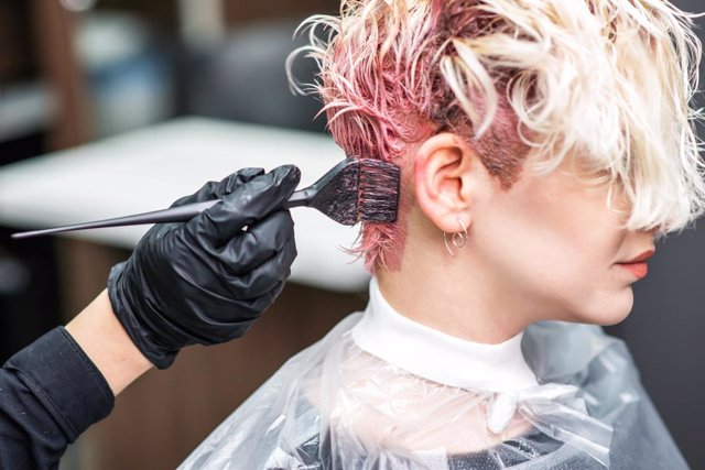 Mujer tiñéndose el pelo en una peluquería, tinte.