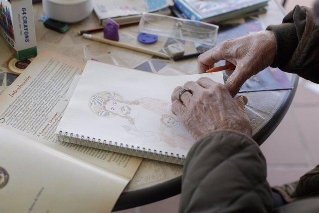 Una anciana realitza un dibuix a l'interior de la Residència de Majors Jesús del Bon Amor on els treballadors sanitaris treballen per cuidar als residents que allí viuen en plena pandèmia del Covid-19. En Griñón, Madrid, (Espanya), a 27 d'abril