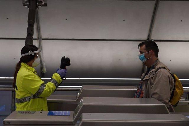Una voluntaria de la DYA toma la temperatura con una pistola a un viajero en la estación de metro de Otxarkoaga. En Bilbao (Vizcaya, País Vasco, España), a 11 de mayo de 2020.