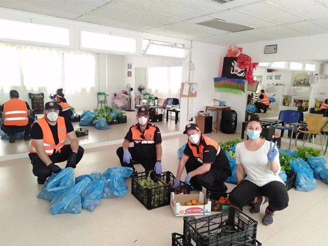 Voluntaris de la Federació d'Associacions Gitanes de Catalunya reparteixen aliments als barris a Barcelona, amb el suport del Banc dels Aliments i Mercabarna