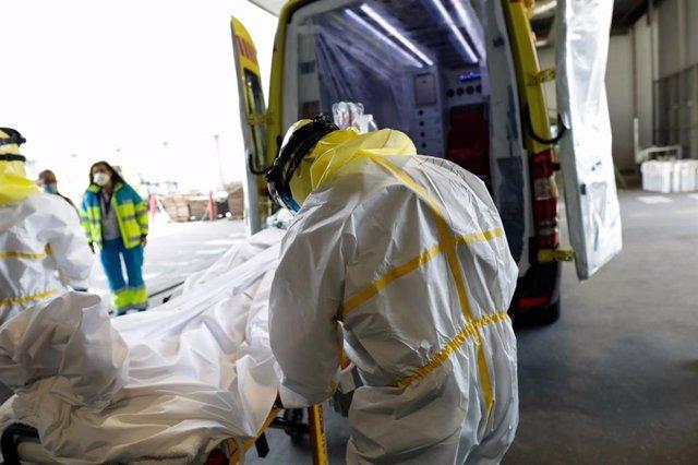 Sanitarios del SUMMA protegidos con un traje protector frente al Covid-19 trasladan a un paciente desde la UVI de IFEMA al interior de la unidad móvil para su posterior traslado al Hospital Puerta de Hierro