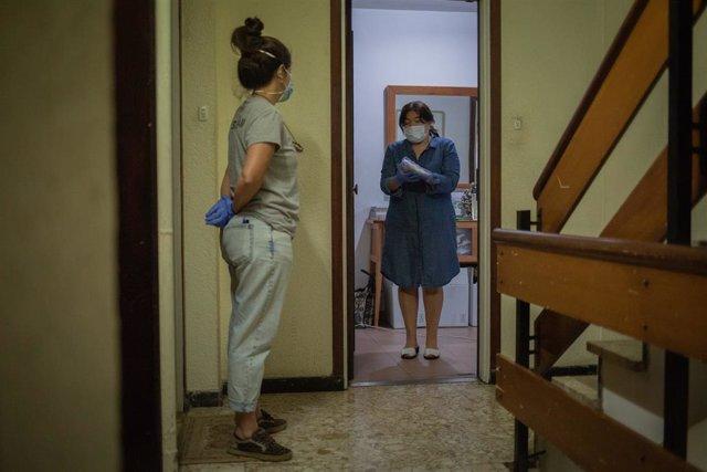Una voluntria de l'ONG Proactiva Open Arms entrega a una dona material sanitari en plena crisi del Covid-19. A Barcelona, Catalunya, (Espanya), a 8 de maig de 2020.