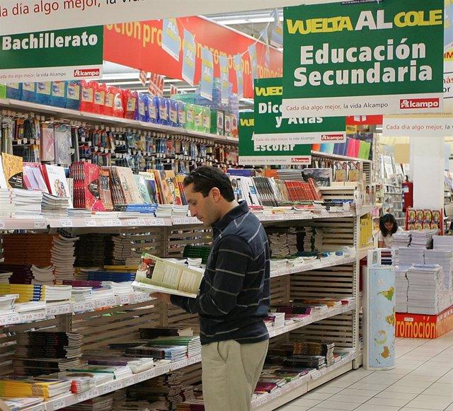 Un hombre ojea libros de texto en un centro comercial.