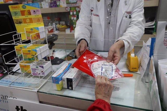 Un farmaceútico entrega a un cliente una de las siete millones de mascarillas FFP2 modelo KN95