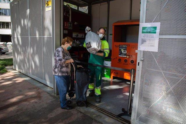 Una dona porta una borsa a un dels punts verds de Barcelona que han obert avui després de la reincorporació de 1.000 operaris de neteja del servei municipal durant la fase 0 de la desescalada a la ciutat