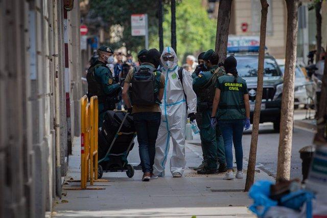 Agents de la Guàrdia Civil totalment protegits surten d'un domicili del carrer de Josep Anselm Clavé en el districte de Ciutat Vella de Barcelona on han detingut a un presumpte gihadista que cercava objectius sota l'estat d'alarma
