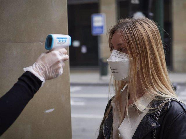 Una trabajadora de la tienda de moda Urban Sons le toma la temperatura a una clienta