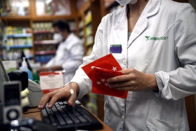 Una farmacéutica registra antes de entregarla a un cliente una de las siete millones de mascarillas FFP2 modelo KN95 que se reparten en la Comunidad de Madrid.