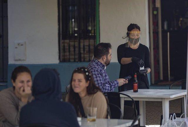 Una camarera atiende la terraza de un bar, el día en el Sevilla pasa a la fase 1 del plan de desescalada que ha elaborado el Gobierno de España. En esta fase, las terrazas de los restaurantes y establecimientos del sector de la hostelería, pueden estar ab