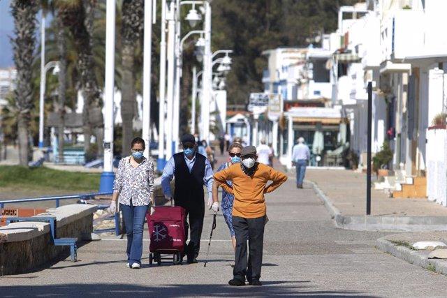Personas mayores recorren el paseo marítimo por la zona de La Malagueta