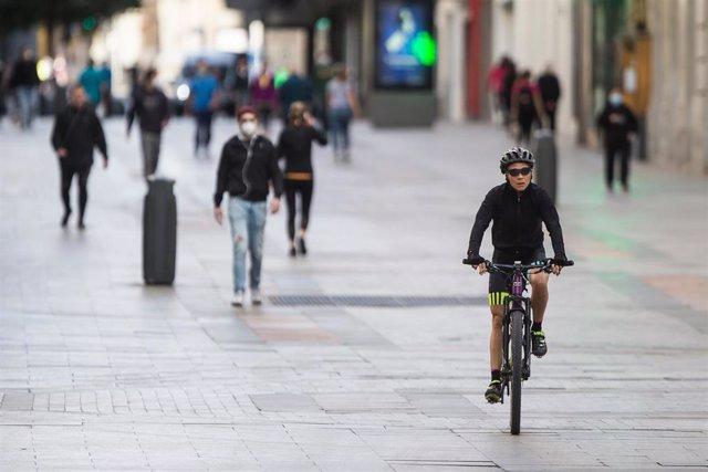 Varias personas realizan deporte en bicicleta por la Calle Preciados de Madrid