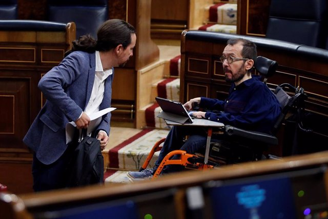 El vicepresidente segundo del Gobierno, Pablo Iglesias, conversa con el portavoz de Unidas Podemos, Pablo Echenique, durante un Pleno del Congreso