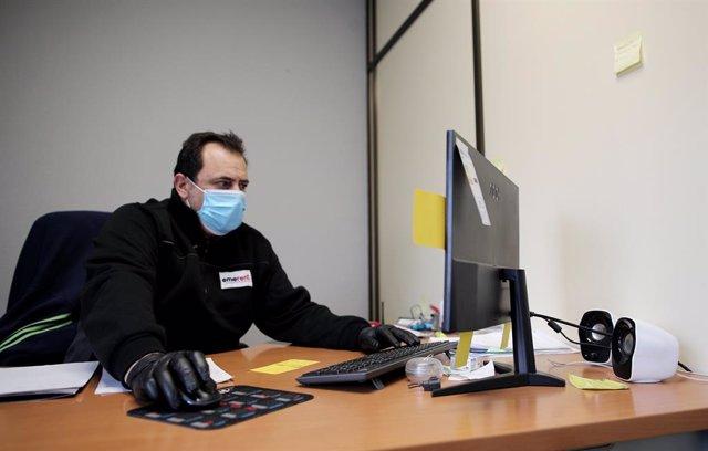 Un operari protegit amb una mascarilla i guants treballa des de l'ordinador, a Madrid (Espanya), a 14 d'abril de 2020.