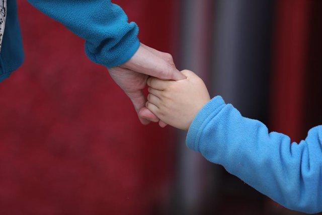 Un nen camina de la mà durant el confinament per coronavirus (Arxiu)