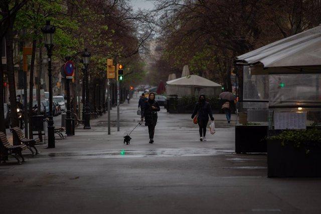 Una dona passeja el seu gos durant el segon dia laborable de l'estat d'alarma pel coronavirus, a Barcelona (Espanya), a 17 de març de 2020.