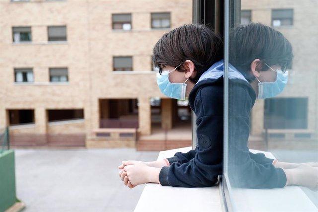 Un niño con una mascarilla se asoma a la ventana de su casa cuando queda tan solo una semana para que niños y preadolescentes puedan salir a la calle durante el confinamiento por el coronavirus, en Valdemoro/Madrid (España) a 20 de abril de 2020.