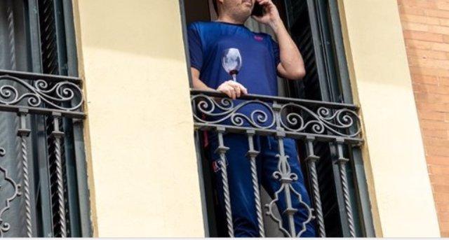 Un hombre en el balcón de su casa con una copa de vino