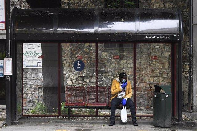 Un hombre con mascarilla espera un autobús en Italia