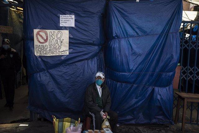 Un vendedor ambulante ante la entrada de un mercadillo cerrado por el coronavirus en Bolivia.