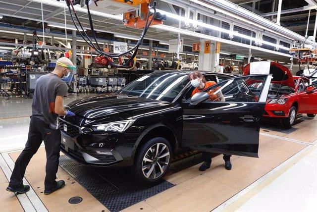 Dos trabajadores en la línea de producción del Seat León en la fábrica de Martorell (Barcelona)