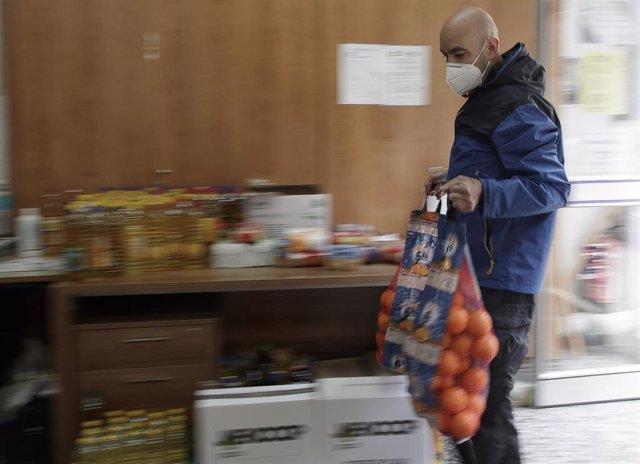 Voluntarios de la Asociación de Vecinos Parque Aluche colocan alimentos y productos dentro de su sede ubicada en la calle Quero n 69