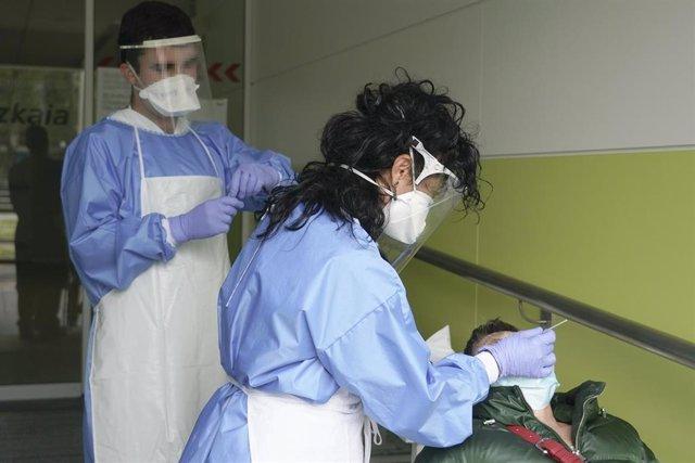 Dos sanitarios protegidos con guantes, mascarillas y pantallas protectoras recogen una muestra para realizar un Análisis PCR