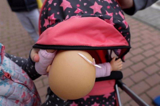 Una niña pasea por la calle empujando un carrito con un bebé de juguete. En Madrid (España) a 27 de abril de 2020.