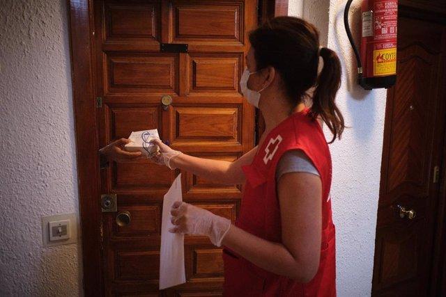 Una voluntaria de Cruz Roja entrega medicamentos en una vivienda durante la pandemia del COVID-19 en Málaga
