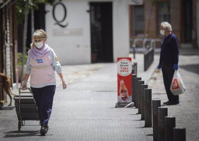 Una mujer con mascarilla, guantes y un carrito de la compra camina por la calle.