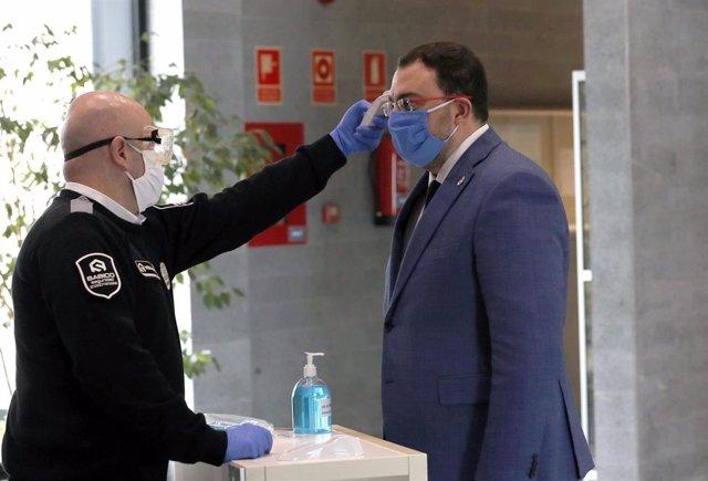 Un operario toma la temperatura al presidente del Principado, Adrián Barbón, a su llegada a las instalaciones del 112 en La Morgal.