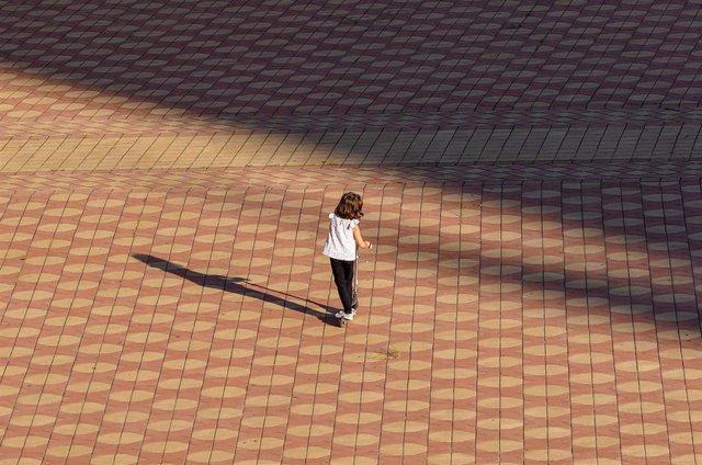 Una niña jugando con un patinete en la Plaza de España, en Sevilla a 29 de abril del 2020