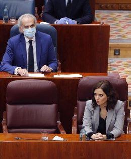 La presidenta de la Comunidad de Madrid, Isabel Díaz Ayuso (d) junto a su consejero de Sanidad, Enrique Ruiz Escudero (atrás) durante el pleno en la Asamblea de Madrid.