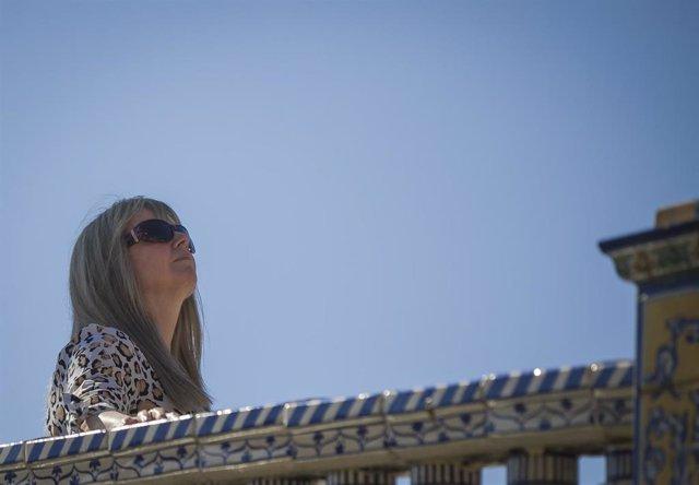 Aumento de temperaturas. Turista se protege con gafas de sol. En la Plaza de España, Sevilla a 04 de febrero de 2020.