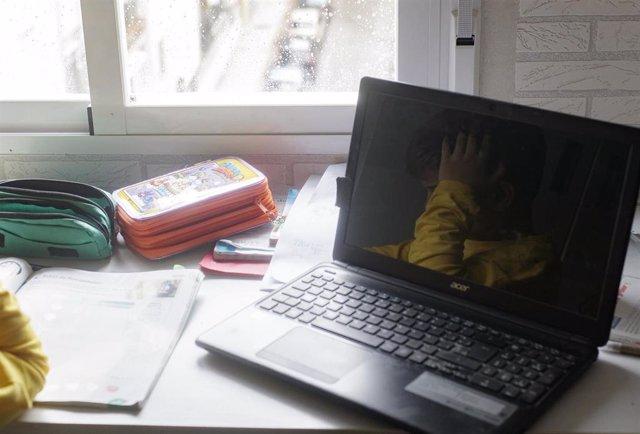 Un niño estudia junto a un ordenador portátil en su domicilio de Madrid durante el confinamiento.