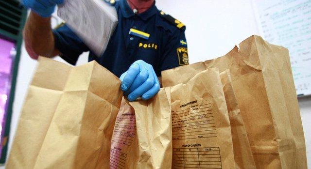 Policías forenses examinando las pruebas recogidas en la escena de un crimen.