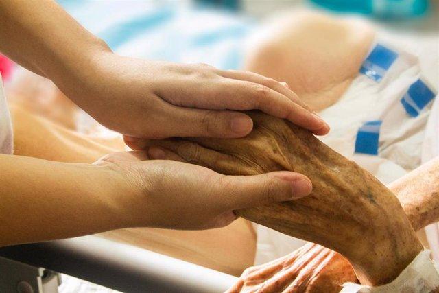 Una trabajadora de una residencia coge la mano a una usuaria. Ancianos, dependencia