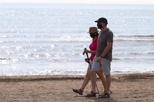 Dos personas protegidas con mascarilla pasean por la playa de la Malvarrosa durante su franja horaria permitida en la desescalada ante la crisis del Covid-19 en la que mayores de 14 años y menores de 69 tienen permitidas las salidas para pasear y hacer de
