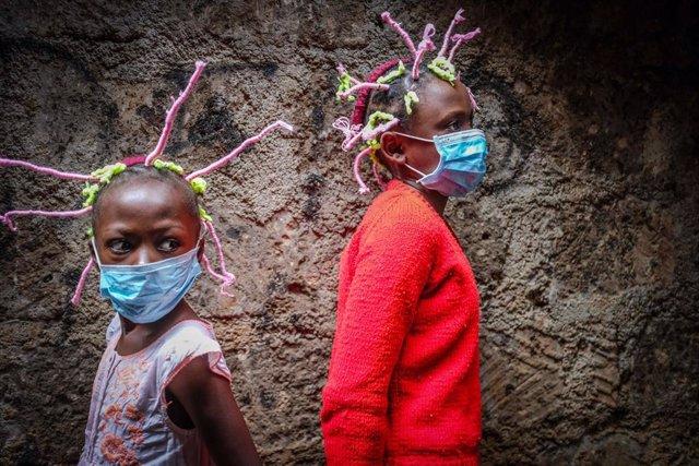 Dos niñas con mascarilla y peinados de 'coronavirus' en Nairobi
