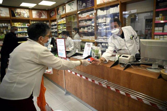 Un farmacéutico entrega a una cliente una de las siete millones de mascarillas FFP2