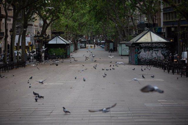 La Rambla de Barcelona amanece vacía un día marcado por la festividad de Sant Jordi, que a diferencia de otros años