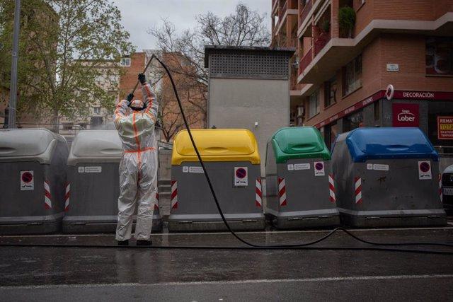 Un treballador desinfecta i neteja els contenidors d'escombraries, a 1 d'abril de 2020. (arxiu)