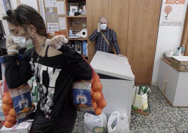 Voluntarios de la Asociación de Vecinos Parque Aluche colocan alimentos en la calle Quero n 69 para luego repartirlos el fin de semana. En Aluche, Madrid, (España), a 13 de mayo de 2020.