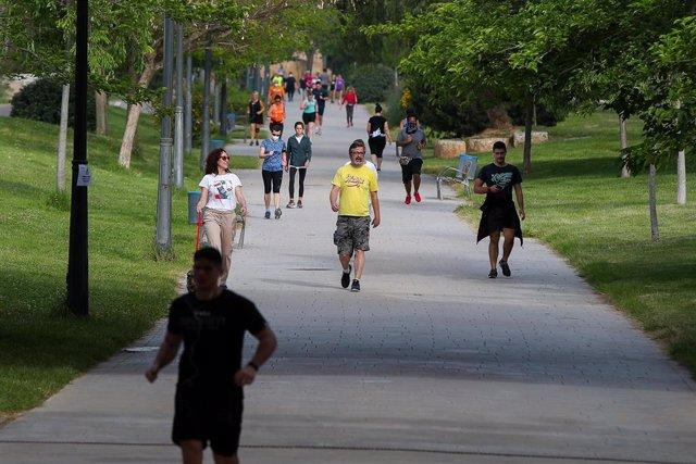Personas caminan por el parque del Río Turia durante su franja horaria permitida en la desescalada ante la crisis del Covid-19 en la que mayores de 14 años y menores de 69 tienen permitidas las salidas para pasear y hacer deporte