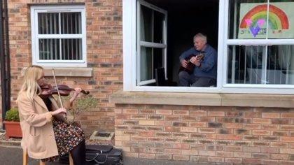 Esta mujer toca el violín para sorprender a su abuelo, de 72 años, en aislamiento por la crisis del coronavirus