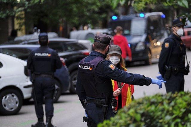 Un policía nacional da una indicación a una mujer en la concentración de protesta contra Sánchez en la calle Núñez de Balboa de Madrid