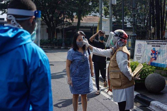 Un profesional sanitario toma la temperatura a una mujer en Indonesia, en el marco de la pandemia del coronavirus.