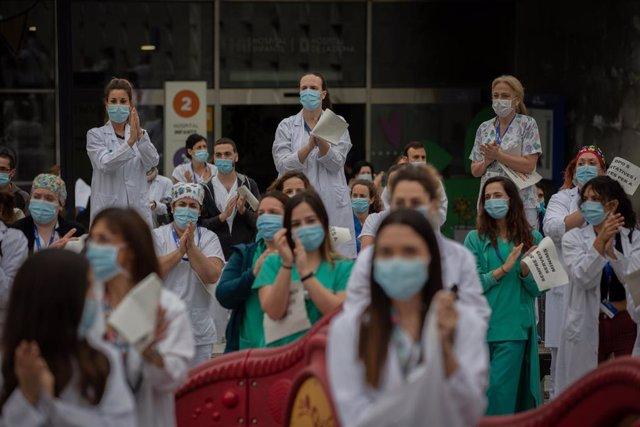 Decenas de miembros del personal sanitario protegidos con mascarilla sostienen carteles durante la concentración de sanitarios en el Día Internacional de la Enfermería a las puertas del Hospital Vall d'Hebron. En Barcelona, a 12 de mayo de 2020.