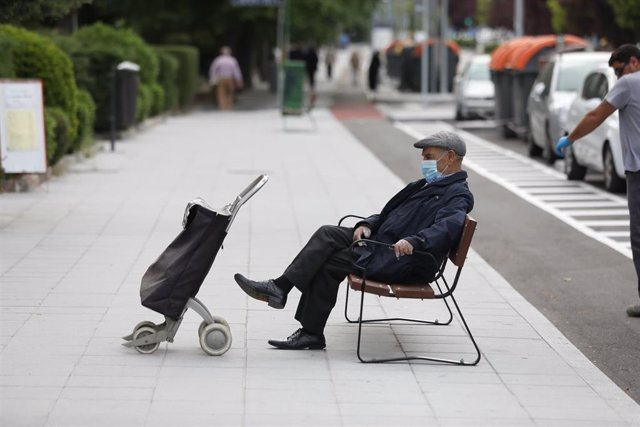 Un hombre de edad avanzada espera en un banco protegido con mascarilla y con un carro de la compra durante su franja horaria permitida en la desescalada por la crisis del Covid-19 donde aquellos mayores de 70 años pueden salir a la vía pública de 10.00 a