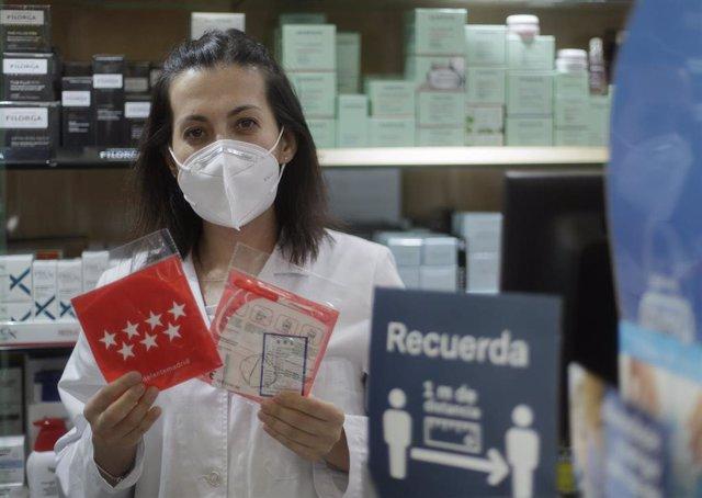 Una farmacéutica muestra una mascarilla en la Farmacia CEA, una de las 2.882 farmacias madrileñas que desde el pasado lunes han entregado de forma gratuita siete millones de mascarillas FFP2 modelo KN95. En Madrid, (España), a 12 de mayo de 2020.